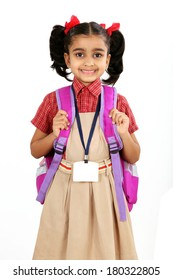 Indian primary school girl in uniform with school bag over shoulder. Isolated on white.