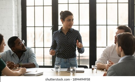 Indian project leader and diverse mates gathered in boardroom brainstorming making sales analysis. Female business trainer teach multiracial apprentices during corporate training. Mentoring concept