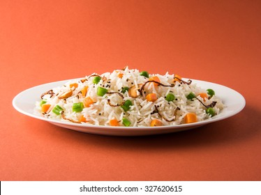 Indian Pulav or veg biryani made using Basmati Rice served in a white oval shape ceramic plate, selective focus