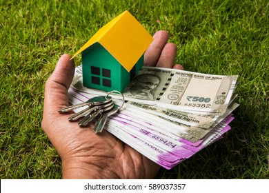 Indian Real estate business concept showing 3D model house with keys, paper currency notes and Calculator. Selective focus
