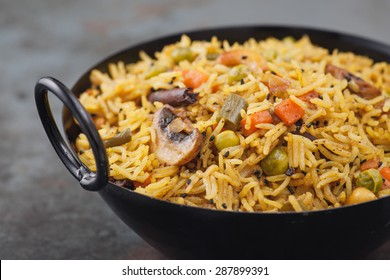 Indian rice dish vegetarian pulao in the black bowl. With copy space