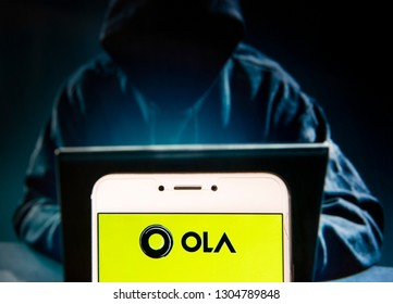 Indian ride-sharing transportation network company Ola Cabs logo is seen on an Android mobile device with a figure of hacker in the background.