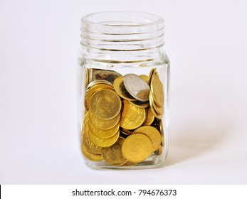 Indian Rupee coins in a glass jar against white background.