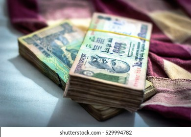 Indian rupee currency, money with blurry Indian blanket on background. Focus on Gandhi. One hundred rupees in packs.