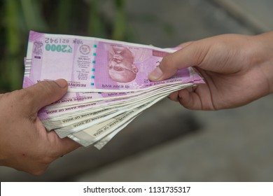 Indian rupees. Holding and giving Indian rupees to someone
