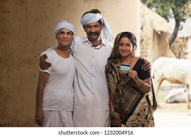 Indian rural farmer family holding credit card