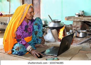 Indian Rural Old lady works on laptop at her open traditional Kitchen in Background. Reach of technology in India. Scope of Technology in Rural India.