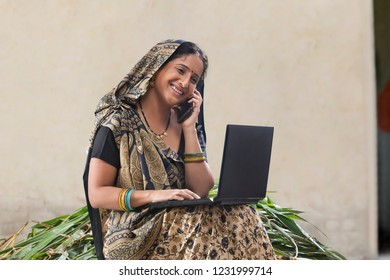 Indian rural woman using laptop and talking on mobile phone