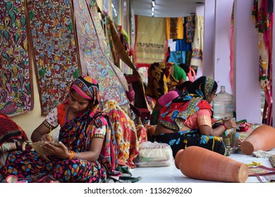 Indian rural women artist are paintings sitting in front of a wall with hanging decorations Indian lifestyle