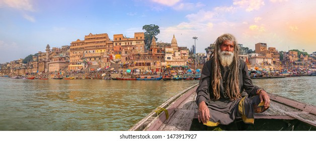 Indian Sadhu on a wooden boat on river Ganges with panoramic view of Varanasi city architecture at sunset