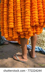 Indian salesman covered with marigold flowers garland on the flower market in Kolkata, India
