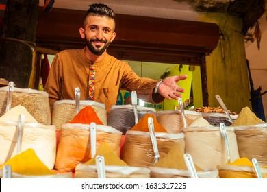 indian sallerman showing his small shop on arambol goa market