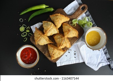 Indian samosa deep fried snack on a black background top view.