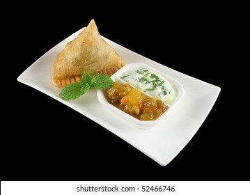 Indian samosa with mango chutney and herb yogurt.