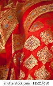 an Indian Sari with orange fabric and Gold thread