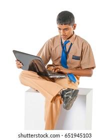 Indian School boy doing study on laptop, isolated on white background, Mumbai, Maharashtra, India, Southeast Asia.