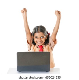Indian School girl with laptop raise hands and celebrate his victory, isolated on white background, Mumbai, Maharashtra, India, Southeast Asia.