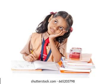 Indian School girl thinking while study in classroom,, isolated on white background, Mumbai, Maharashtra, India, Southeast Asia.