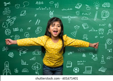 Indian school kid in hand stretched pose standing over green chalkboard background full of doodles