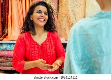 indian seller women in red kurta stand in her studio showroom