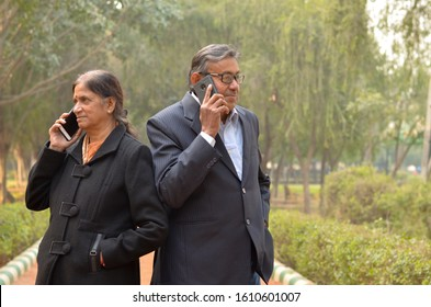 Indian Senior citizen husband and wife couple using their smart phones with their back against each other in a park in New Delhi, India. Nowadays old people are obsessed with mobiles. Concept love