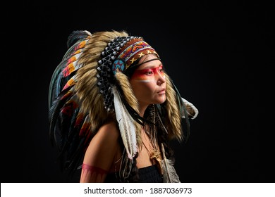 indian shamanic female with Indian feather wearing and colorful makeup, posing at camera isolated over black background. portrait side view