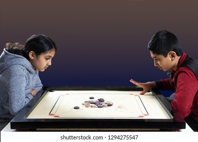 Indian Siblings Playing Carrom on a Carrom Board