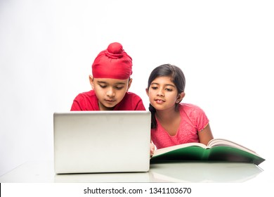 Indian sikh/Punjabi  boy and girl studying with books and laptop computer at study table