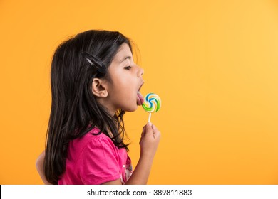 indian small girl with lolipop or loly pop, asian girl and lolipop or lolypop, playful indian cute girl posing with lolipop or candy