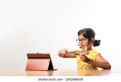 Indian small girl student making or measuring wings of paper plane or Aeroplane, doing school project or learning science with online tutorial