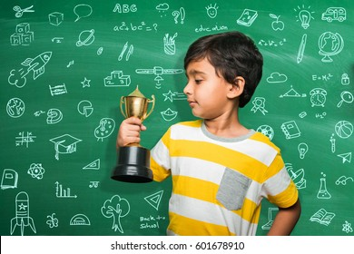 indian small school kid holding trophy or winning cup, asian boy standing over green chalkboard background with doodles drawing with cup