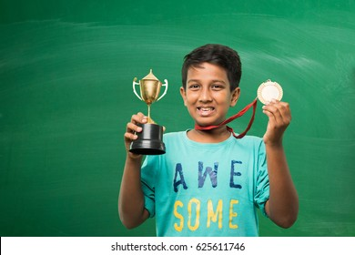 indian smart boy or school kids holding gold medal and trophy cup over green chalkboard background