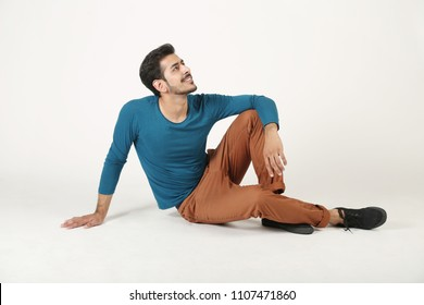 Indian smart boy is sitting on the floor with smiling face on white background.