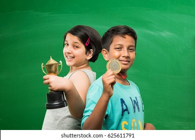 indian smart school girl and boy holding gold medal and trophy cup over green chalkboard background