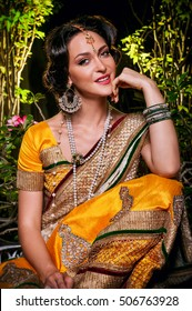 Indian smile beautiful girl sitting in in a yellow sari and jewelery with pearls,looks like royalty