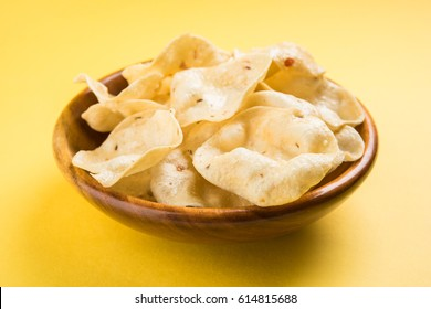Indian snack deep fried Papad or Papadum, served in a bowl over moody background. Selective focus