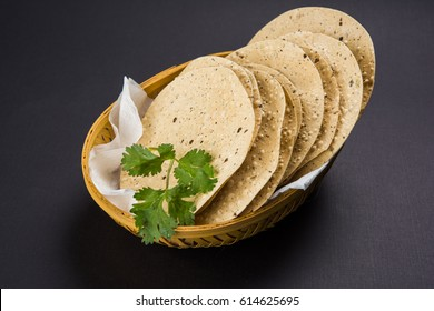 Indian snacks, deep fried or roasted Mung/Urad dal crackers or papad which is a side dish in lunch and dinner. Served in a cane basket /plate with Coriander leaf. Selective focus showing macro details