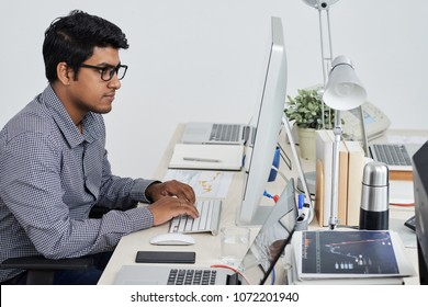 Indian software developer working on computer at his office table