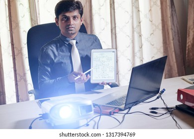 Indian software engineer showing flowchart of tablet computer when speaking at presentation or conference