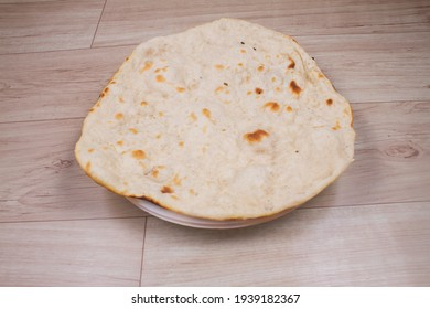 indian special flat bread also known as tandoori roti or naan, served in a white ceramic quarter plate