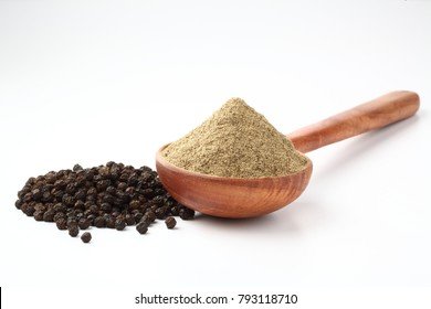 Indian spices Black Pepper powder in a wooden spoon with pepper corns on white background