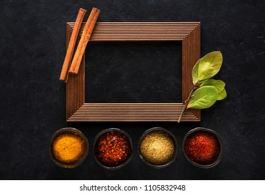 Indian spices in bowls and empty wooden frame for text on black concrete background, top view