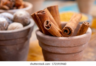 Indian spices collection, dried aromatic cinnamon barks and another spices in clay bowls close up