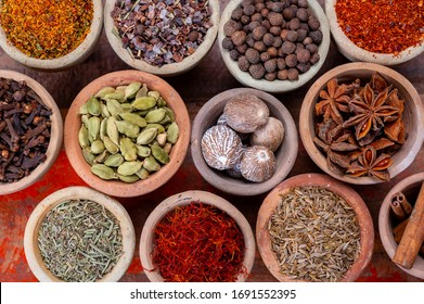 Indian spices collection, dried colorful condiment, nuts, pods and seeds and another spices in clay bowls top view