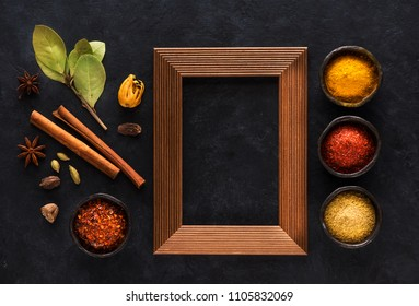 Indian spices and empty wooden frame for text on black concrete background, top view, flat lay