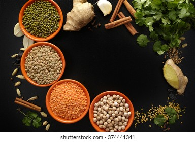 Indian spices, four bowls with pulse, legumes, fresh coriander, ginger, garlic and dried cardamom, cloves, cinnamon on black background, copy space