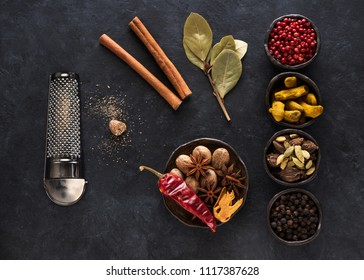 Indian spices and herbs in bowls on a black concrete background, top view, flat lay