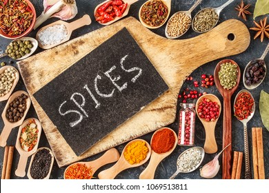 Indian spices, herbs and empty  cutting board on black background.  Colorful spices, top view. Organic food, healthy lifestyle, space for text