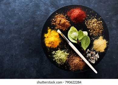 Indian spices and herbs on a black concrete background