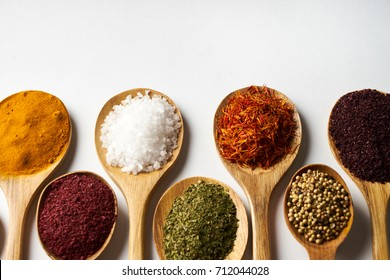 Indian spices isolated on white background with copy space. Colorful spices in wooden spoon. Ingredients of asian cuisine spices